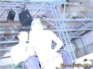 blond buxomy honey spray on public stage